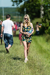 © Licensed to London News Pictures. 13/06/2014. Isle of Wight, UK.   A girl in a pretty floral dress carries water to her tent at Isle of Wight Festival 2014 - today is expected to be the hottest day of the year in the UK.   The Isle of Wight festival is an annual music festival that takes place on the Isle of Wight. Photo credit : Richard Isaac/LNP