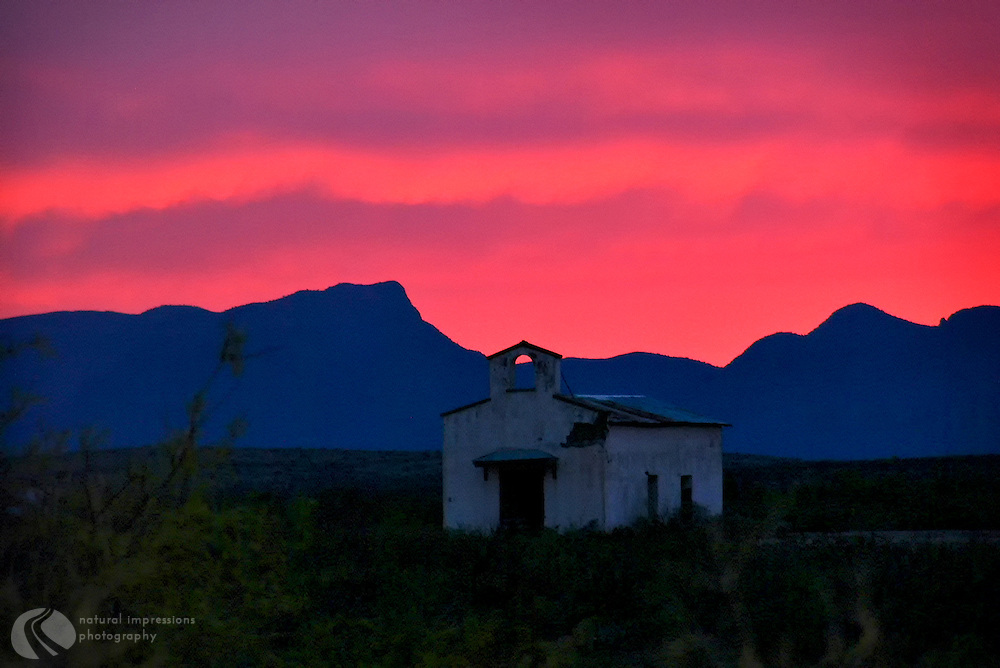 Below an evenng sky filled with neon colors, an old church rests near Balmorhea, Texas.