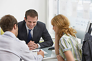 Couple with real estate agent in office man writing
