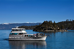 Passengers on a tour boat pass between Fannette Island and Vikingsholm, Emerald Bay State Park, Lake Tahoe, California.