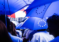 Tourist take a boat tour in the canals of Bruge, with umbrellas of the European Union