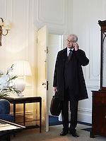 Business man standing in room using mobile phone