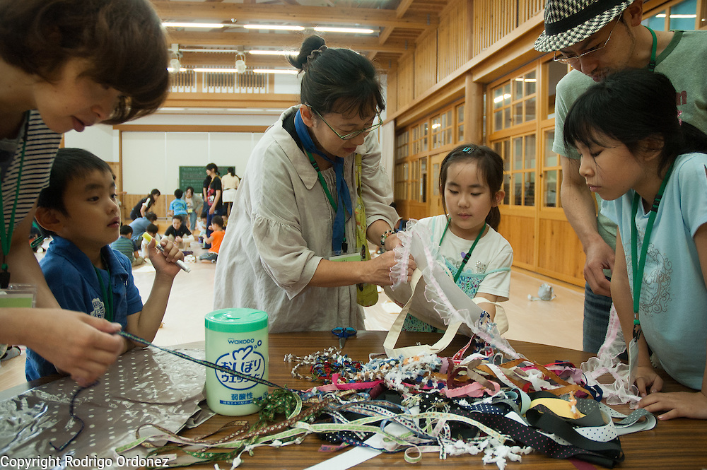 Haruna and her mother Yoko Suzuki (center) participate in handicrafts activities during a summer camp for children from Fukushima, Japan.