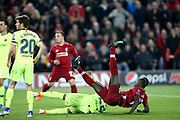 Liverpool forward Sadio Mane (10) is upended in the box but Barcelona players watch as Liverpool midfielder Georginio Wijnaldum (5) puts the loose ball away to score during the Champions League semi-final, leg 2 of 2 match between Liverpool and Barcelona at Anfield, Liverpool, England on 7 May 2019.