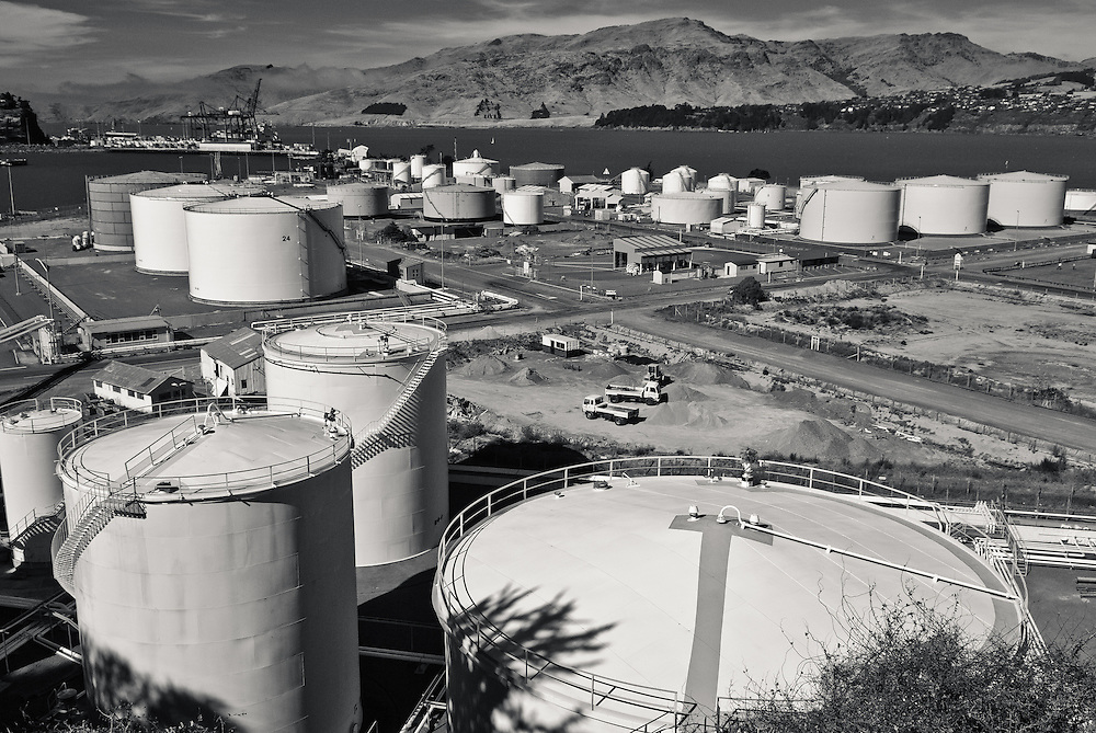Black & white view over a tank farm and cargo terminal at Lyttelton, Post of Christchurch, New Zealand, to the harbour waters and Banks Peninsula mountains