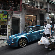 """A woman carries collected card board for recycling past a bles Porche to a collection point down the steep streets in Mid Levels.<br /> <br /> Hong Kong (香港; """"Fragrant Harbour""""), officially known as Hong Kong Special Administrative Region of the People's Republic of China since the hand-over from the United Kingdom in 1997 under the principle of """"one country, two systsems"""".  7 million people live on 1,104km square, making it the most vertivcal city in the world. Hong Kong is one of the world's leading financial centres along side London and New York, it has one of the highest income per capita in the world as well the moste severe income inequality amongst advanced economies. The Hong Kong civil society is highly regulated but has at the same time one of the most lassiez-faire economies with low taxation and free trade. Civil unrest and political dissent is unusual but in 2014 the Umbrella Movenment took to the streets of Hong Kong demanding democracy and universal suffrage. 93 % are ethnic Chinese, mostly Cantonese speaking."""