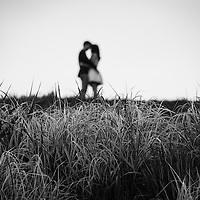 An out of focus couple in each others arms at the top of a hill with tall grasses in foreground.