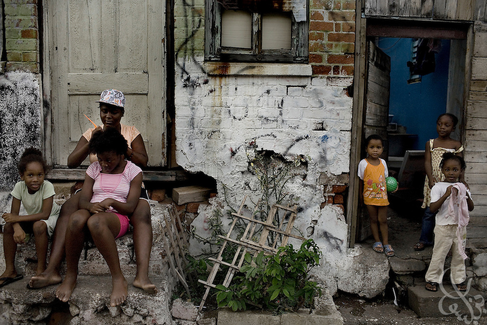 A Jamaican family sits out front of their tenement yard housing in the Matthews Lane area of Kingston June 16, 2008.  A recent United Nations report found that the great majority of victims of violent crime in Jamaica live in ghetto areas, and suffer disproportionately high rates of unemployment, limited clean water supplies and electricity. .