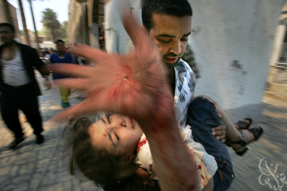 An injured Iraqi schoolgirl is evacuated from the Aqida girls' school near the scene of a suicide car bombing in Tahrir square in Baghdad Saturday May 7, 2005. The bombing, which targeted a passing civilian contractor convoy just outside the school killed at least 22 persons in the late morning explosion in the busy commercial area in the center of Baghdad.