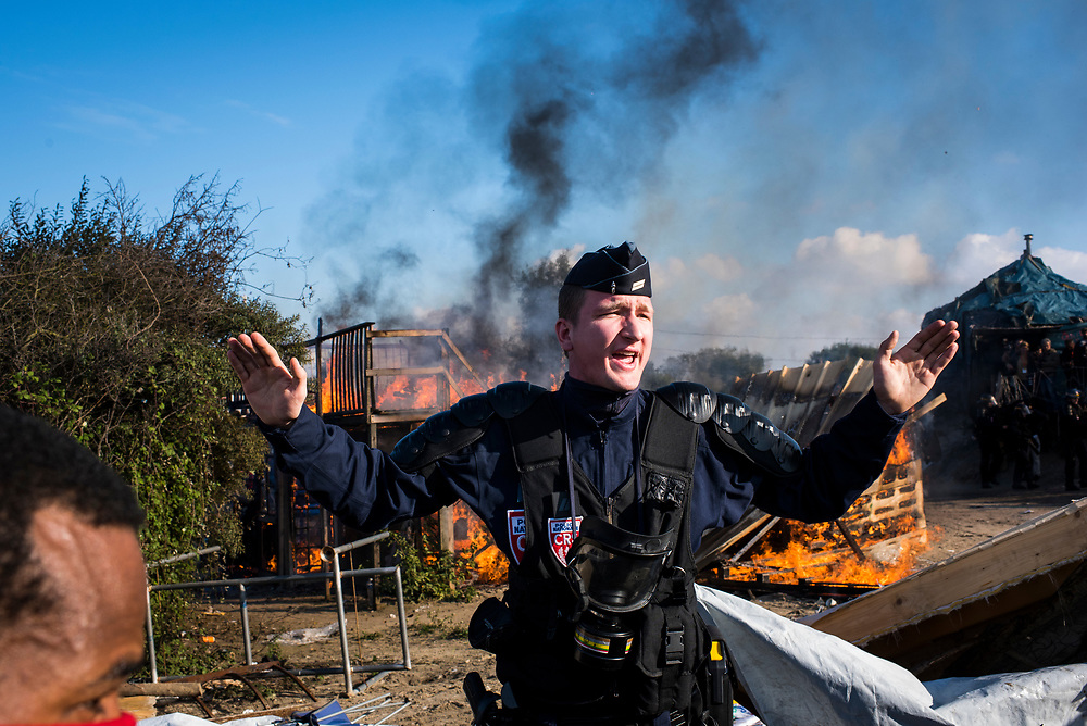 A French law enforcement officer orders onlookers back as a structure burns at The Jungle refugee camp during an operation to evict and relocate the refugees living there on October 25, 2016 in Calais, France.