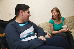 Professional visiting teenager with physical and learning disability at home.