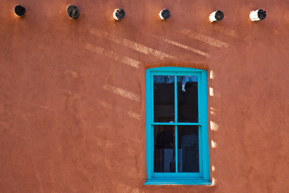 Turquoise blue trim adorns this qunintessential Adobe home on Canyon Road in Santa Fe, New Mexico.