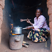 """CAPTION: Fatima has been an improved cookstove user since 2010, when she switched over from using a three-stone fire. """"I used to get through so much wood before"""", she says. """"Now I only need to buy half as much. When cooking nsima, it takes me about 15 minutes; it used to take about 20 to 30 minutes before"""". LOCATION: Chinsapo 2, Lilongwe, Malawi. INDIVIDUAL(S) PHOTOGRAPHED: Fatima Amadu."""