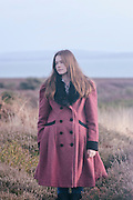 a young woman in a read coat is standing in the heather in winter