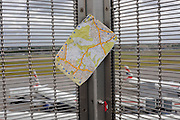 A London A-Z map book is caught in security fencing between gusts of wind at Heathrow airport's Terminal 5.