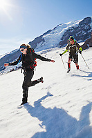 A young man and woman running down the Muir snow field on Mount Rainier, Washington, USA.