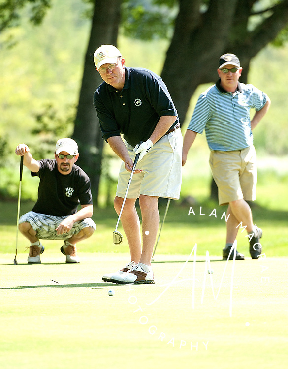 Tom Boucher, left and Tom Noble, right, watch as Peter Marshall putts out on the sixth hole at Waukewan CC during the annual Hale Memorial Tournament on Friday, June 18, 2010.  {Alan MacRae/for the Citizen)