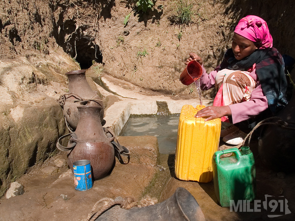 Bekelu Rufo, 22, collecting water from a capped spring near their village in Kotoba, Ethiopia.