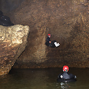 Participants enter the water on black water tubing while Black Water rafting in the Waitomo Glowworm Caves, Waitomo, North Island, New Zealand..The Legendary Black Water Rafting Company is New Zealand's first black water adventure tour operator which takes tourists through the  Ruakuri Cave at Waitomo..The five hour expedition combines abseiling the 35 metre entrance. climbing, a flying fox. black water tubing, leaping and floating through Ruakuri Cave and observing glow worms. The journey concludes  into the sunlight of the Waitomo forest..Waitomo, New Zealand,, 14th December  2010 Photo Tim Clayton