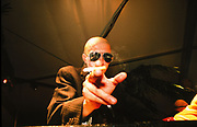 Bald man wearing sunglasses, smoking cigarette in a Paris night club, 1990's