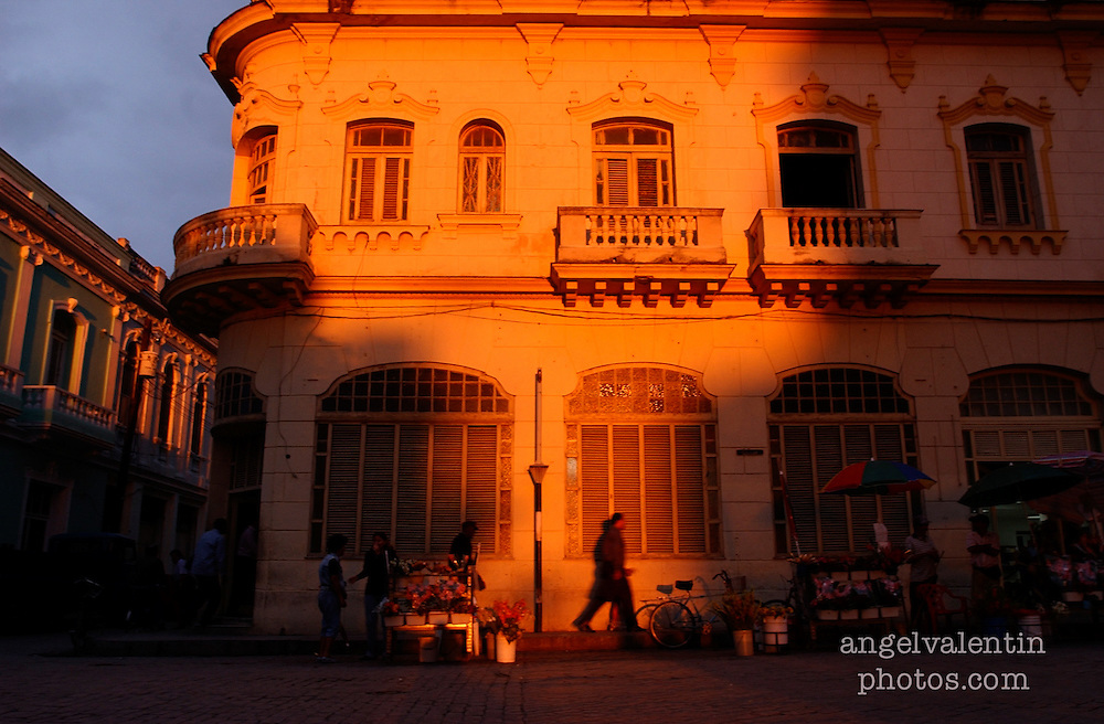 1/29/03---photo by A.Enrique Valentin---<br /> cuba29h----<br /> Pedestrians circulate in the town of  Santa Clara in the province of Villa Clara as the sun rapidly sets casting an orange glow on buildings..