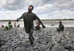 © Licensed to London News Pictures. 12/05/2019. Maldon, UK. Competitors take part in the Maldon Mud Race in Essex. The race originated in 1973 and involves competitors racing around a course on the mudbanks of the river Blackwater at low tide. Photo credit: Peter Macdiarmid/LNP