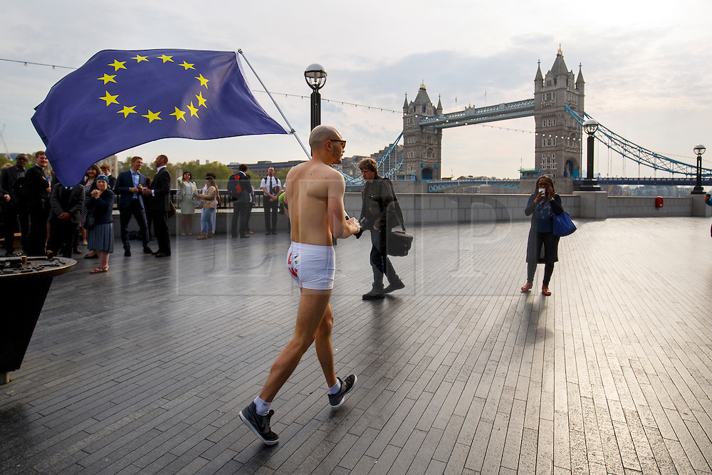 © Licensed to London News Pictures. 09/05/2016. London, UK. A semi-naked man waves the European Union flag in front of Tower Bridge in London on the day that British Prime Minster David Cameron and former Mayor of London Boris Johnson both deliver speeches on Britain's membership of the EU and the upcoming EU referendum. Photo credit: Tolga Akmen/LNP