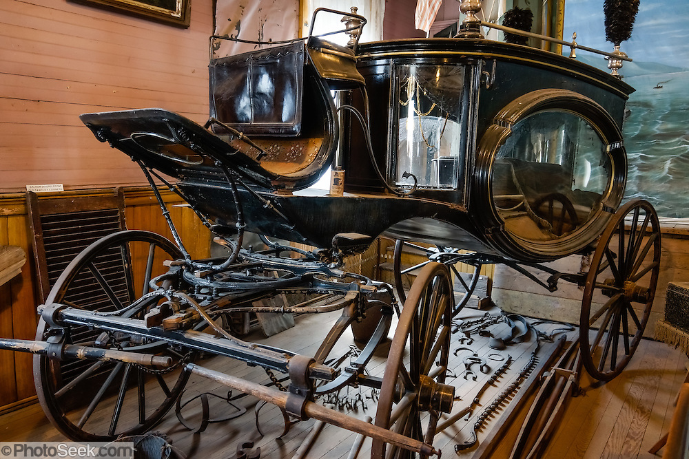 "An historic glass hearse (funeral carriage) is displayed in the Miners Union Hall (which has been turned into the park's Museum & Visitor Center) at Bodie, California's official state gold rush ghost town. Bodie State Historic Park lies in the Bodie Hills east of the Sierra Nevada mountain range in Mono County, near Bridgeport, California, USA. After W. S. Bodey's original gold discovery in 1859, profitable gold ore discoveries in 1876 and 1878 transformed ""Bodie"" from an isolated mining camp to a Wild West boomtown. By 1879, Bodie had a population of 5000-7000 people with 2000 buildings. At its peak, 65 saloons lined Main Street, which was a mile long. Bodie declined rapidly 1912-1917 and the last mine closed in 1942. Bodie became a National Historic Landmark in 1961 and Bodie State Historic Park in 1962."