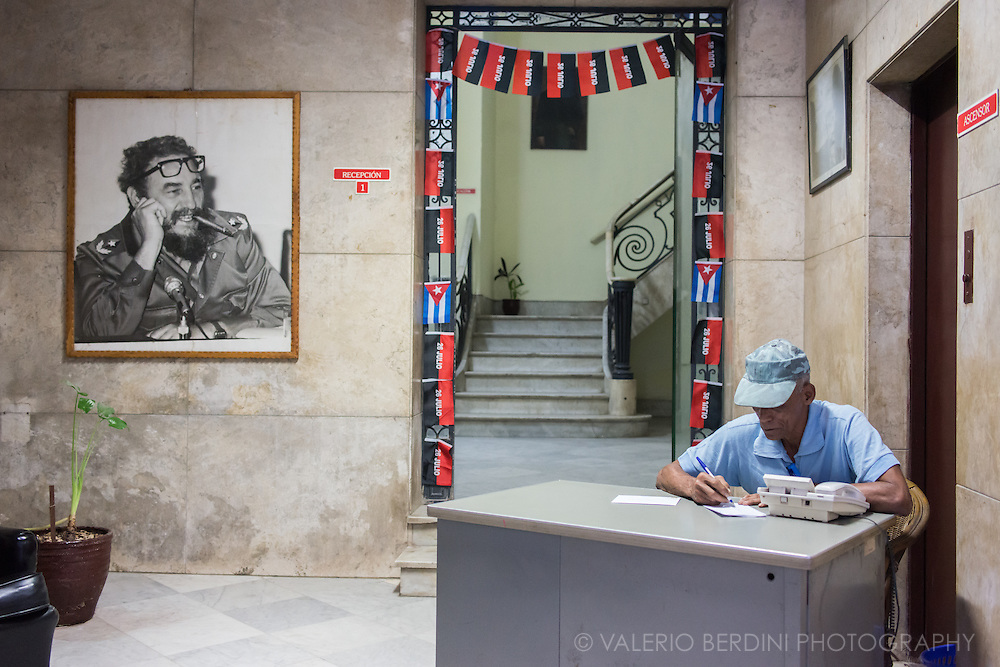 A worker at a desk of a government office in Havana. On the wall a portrait of Fidel Castro, decorating the wall flags of Cuba and of the 26th of July movement, the revolutionary organisation that overthrew Batista dictatorship. Cuba, 2015.