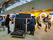 "24 DECEMBER 2015 - BANGKOK, THAILAND: Workers move a baggage x-ray machine through the new domestic terminal at Don Muang (also spelled Don Mueang) International Airport. The new terminal had its ""soft"" opening Dec. 24. Don Muang is the airport used by low cost airlines serving Bangkok and is now the largest airport in the world for low cost carriers. In 2014, more than 21million passengers used Don Muang. Don Muang International Airport is the oldest airport in Asia and one of the oldest airports in the world. It started functioning as an airfield in 1914.     PHOTO BY JACK KURTZ"
