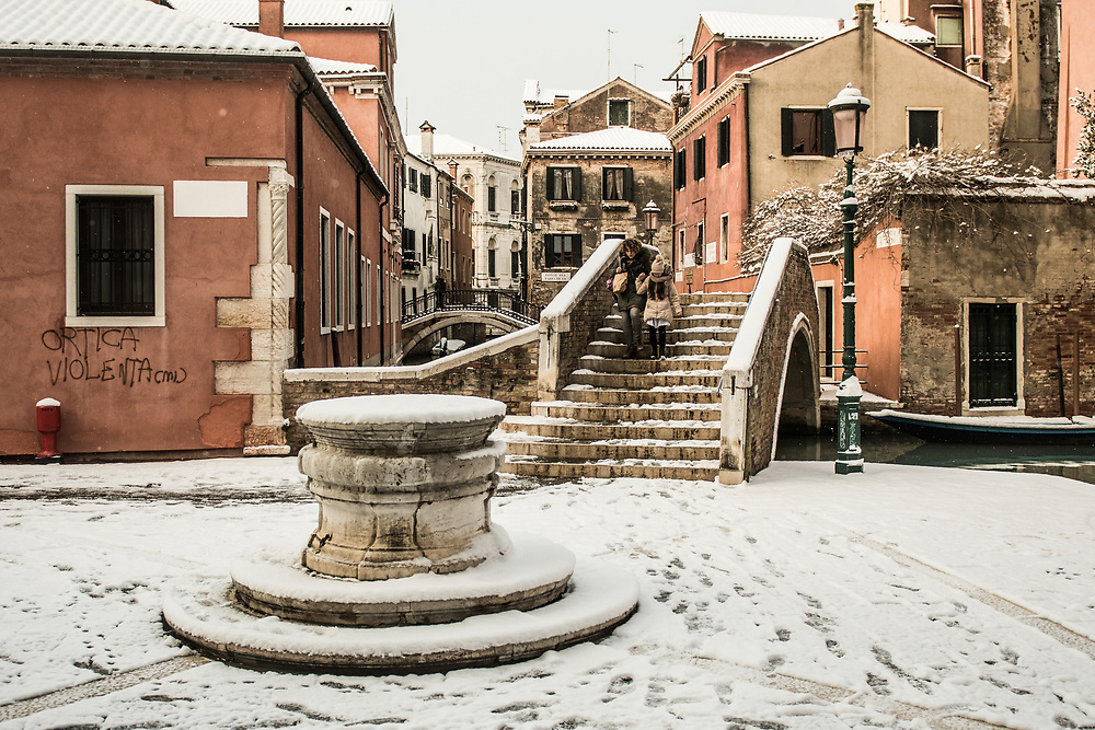 VENICE, ITALY - 28th FEBRUARY/01st MARCH 2018<br /> A woman with her daughter walks cautiosly after a snowfall in Venice, Italy. A blast of freezing weather called the &ldquo;Beast from the East&rdquo; has gripped most of Europe in the middle of winter of 2018, and in Venice A snowfall has covered the city with white, making it fascinating and poetic for citizen and tourists.   &copy; Simone Padovani / Awakening