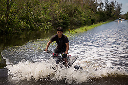 September 11, 2017 - Collier County, Florida, U.S. - A person rides an ATV down a flooded street in southern Collier County on Monday,. Irma made landfall in the area as a category 3 hurricane the prior day. (Credit Image: © Loren Elliott/Tampa Bay Times via ZUMA Wire)