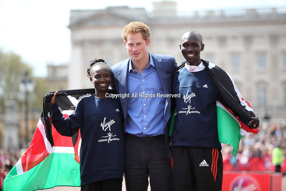 22.04.2012 London, England. Prince Harry poses with the winners of the 2012 Virgin London Marathon Mary Keitany (Kenya) and Wilson Kipsang (Kenya) on the Mall in front of Buckingham Palace.