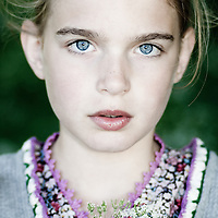 Close up of a young girl with blonde hair and blue eyes holding cow parsley