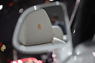 Manhattan, New York, USA. April 12, 2017.  Reflected in 2017 Rolls-Royce Dawn side view mirror is gold embroidered Double R logo stitched on leather headrest of driver's seat, of white convertible, which is on display in Exotics section at the New York International Auto Show, NYIAS, during the first Press Day at the Javits Center.