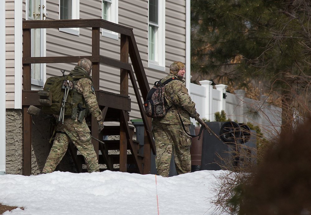 Dedham, MA 03/07/2014<br /> Metro SWAT officers walk behind a home on Leonard St during a standoff in East Dedham on Friday afternoon.<br /> Alex Jones / www.alexjonesphoto.com