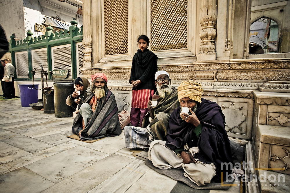 Men and women sit along the walls of the shrine of Nizamuddin waiting for handouts of food and money.
