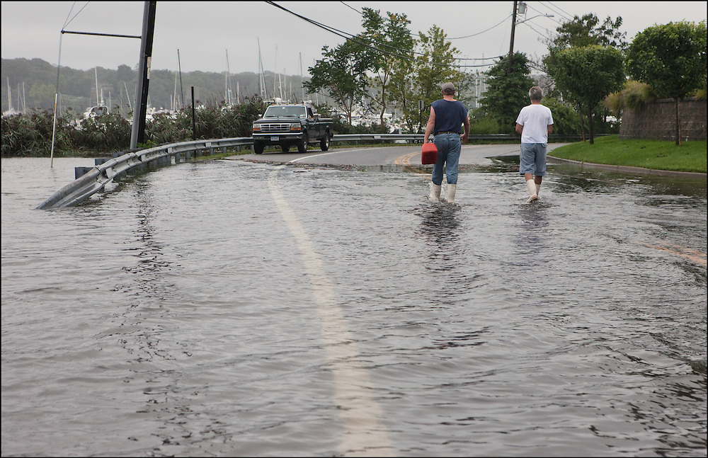Residents of Huntington, New York walk through flooded streets after Hurricane Irene made landfall near Brooklyn, NY pushing waters from the Long Island Sound into Huntington Bay.