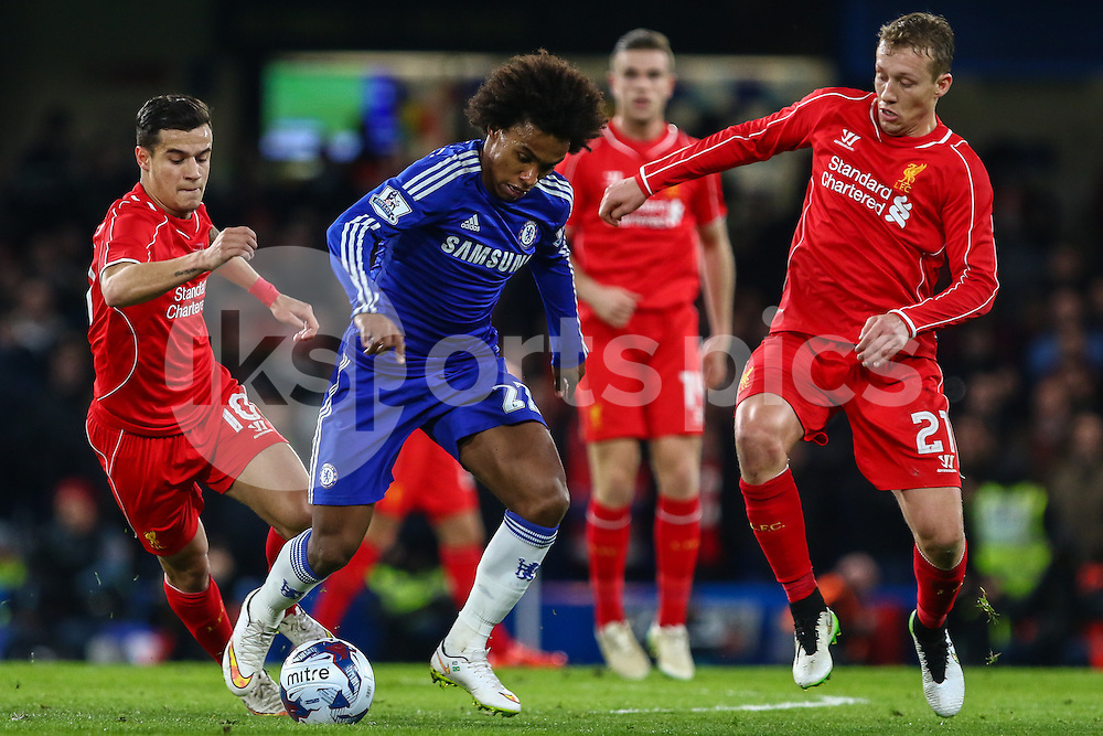 Willian of Chelsea holds the ball under pressure from Philippe Coutinho of Liverpool (left) and Lucas Leiva of Liverpool (right) during the Capital One Cup Semi Final 2nd Leg match between Chelsea and Liverpool at Stamford Bridge, London, England on 27 January 2015. Photo by David Horn.