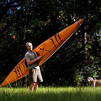 LIVE OAK, FL -- September 30, 2010 -- Boatwright Aaron Wells of Cypress Kayaks LLC, poses for a portrait with his dog, Isabella, and one of his hand-made kayaks at his workshop in Live Oak, Fla., on Thursday, September 30, 2010.  (Chip Litherland for Bay Magazine)