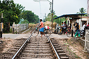 Man with bicycle pass the railroad crossing, Alappuzha