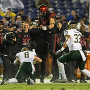 26 November 2016: The San Diego State Aztecs football team closes out the season at home against Colorado State.  San Diego State fullback Nick Bawden (15) leaps over Colorado State defensive back Detrich Clark (8) for a first down. The Aztecs trail the Rams 42-24 at halftime. www.sdsuaztecphotos.com