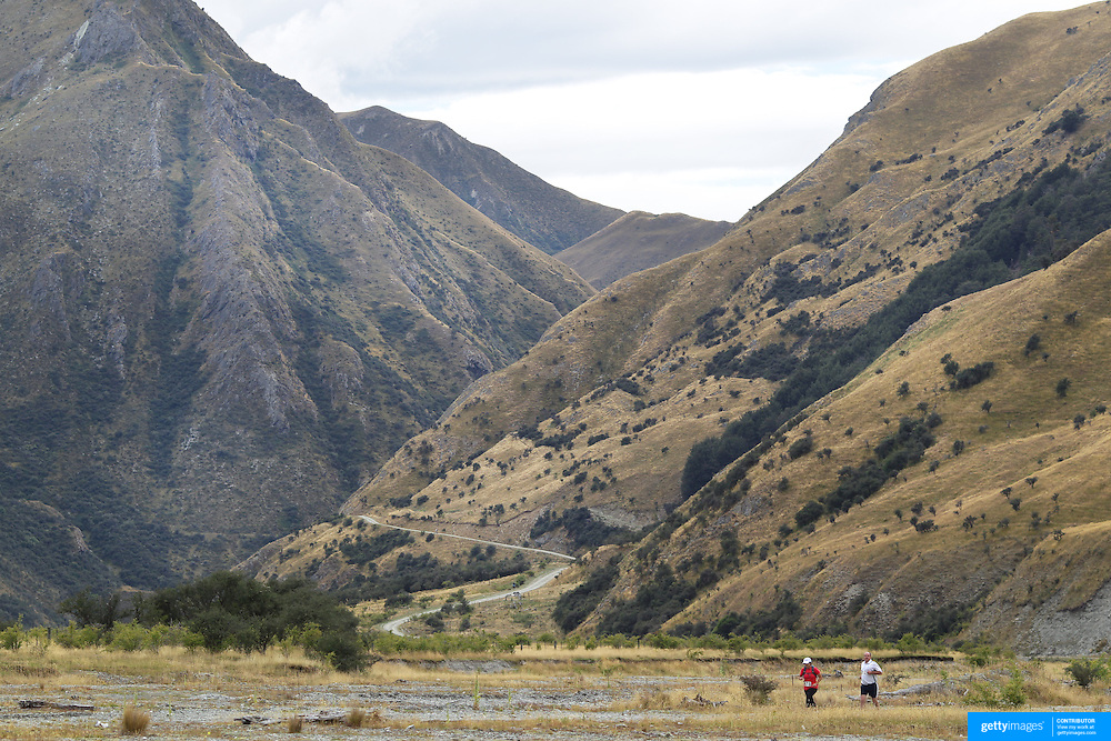 Runners Phillip Chandler and Vicki Paddon cross Moke Creek on the Ben Lomond High Country Station during the Pure South Shotover Moonlight Mountain Marathon and trail runs. Moke Lake, Queenstown, New Zealand. 4th February 2012. Photo Tim Clayton