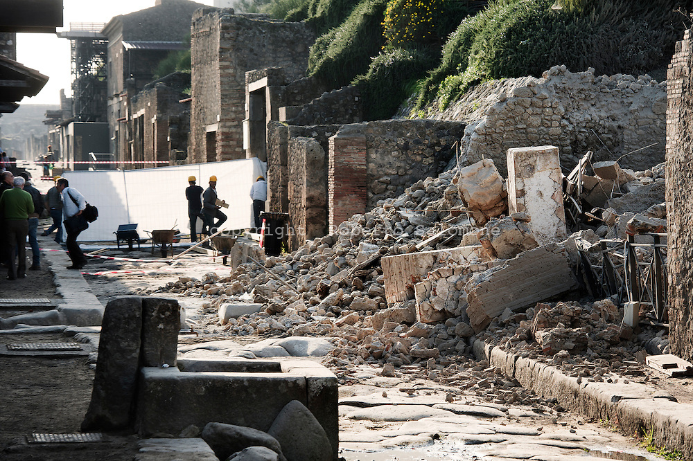 ITALY, POMPEI : People look at the ruins of the Gladiator domus in the archeological site of Pompeii after the house of Roman age collapsed on November 6, 2010. AFP PHOTO / ROBERTO SALOMONE