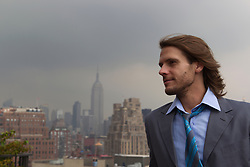 man with long hair on a rooftop over looking New York City Skyline