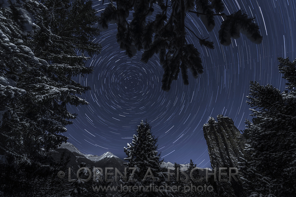 Startrails over the snow covered rock needle Crap Furo on the coldest day since 30 years in the light of the moon, Surava, Parc Ela, Grisons, Switzerland