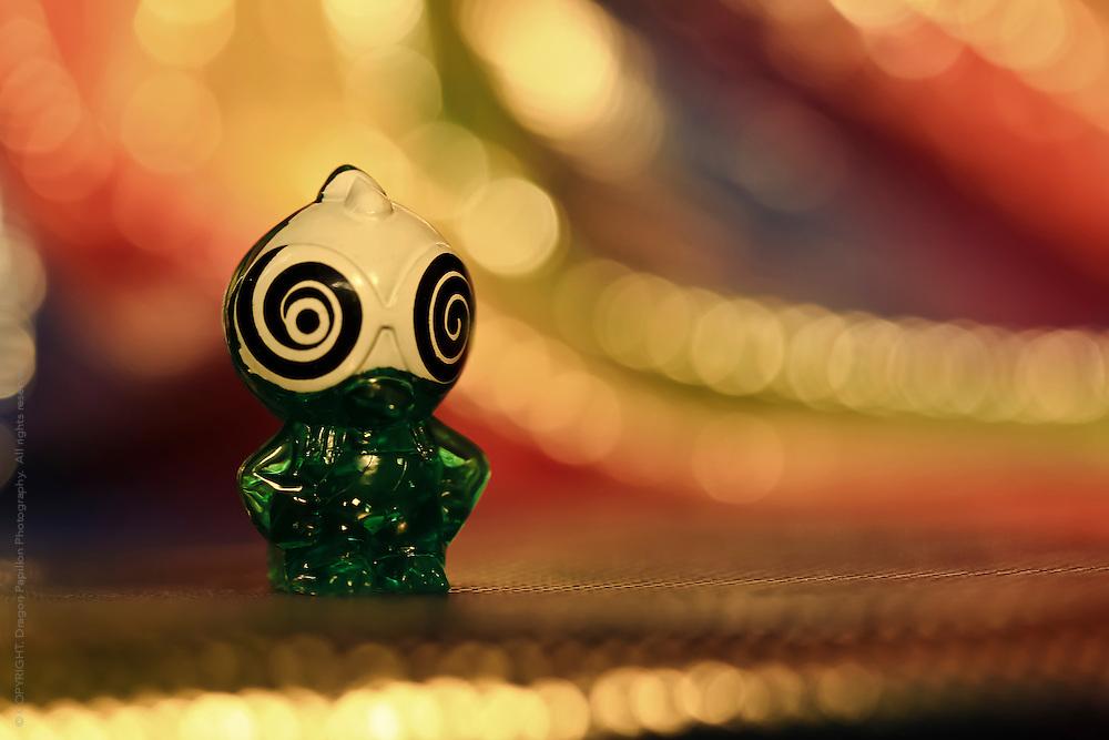 macro image: gogo figurine with hypnotic eyes against colourful bokeh background