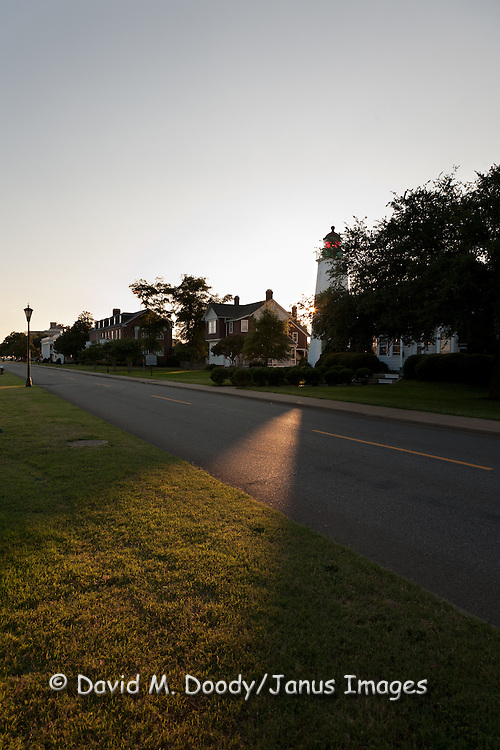 A shaft of sunset light illuminates the road past the Fort Monroe, officer's quarters and Old Point Comfort Lighthouse, Hampton, Virginia