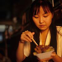 China, Hubei Province, (MR) Lu Jing Bao eats dinner at sunset aboard Yangtze River Ferry near city of Wuhan