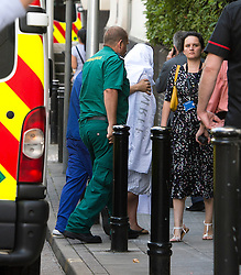 © London News Pictures. 09/08/2013. London, UK. Kirstie Trup (centre) covered in a white sheet being taken into Chelsea and Westminster Hospital after arriving back in the UK. 18 year old Kirstie Trup and her friend Katie Gee were victims of an acid attack while working as charity volunteers in in Zanzibar. Photo credit : Ben Cawthra/LNP